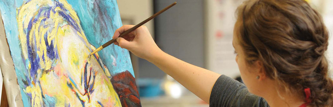 SFA student artist works on a new painting.