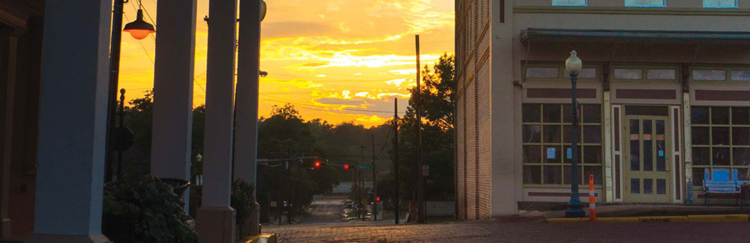 The brick streets of downtown glisten in the sunset.